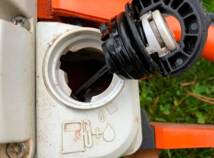Некорректная работа инструмента может быть связана с переполненным баком бензопилы. В этом случае под крышкой кратера будут видны подтеки. Если они есть, проверьте соединение топливной трубки с карбюратором. Она иногда выдавливается при закручивании крышки переполненного бачка. Двигатель может не заводиться по этой причине.